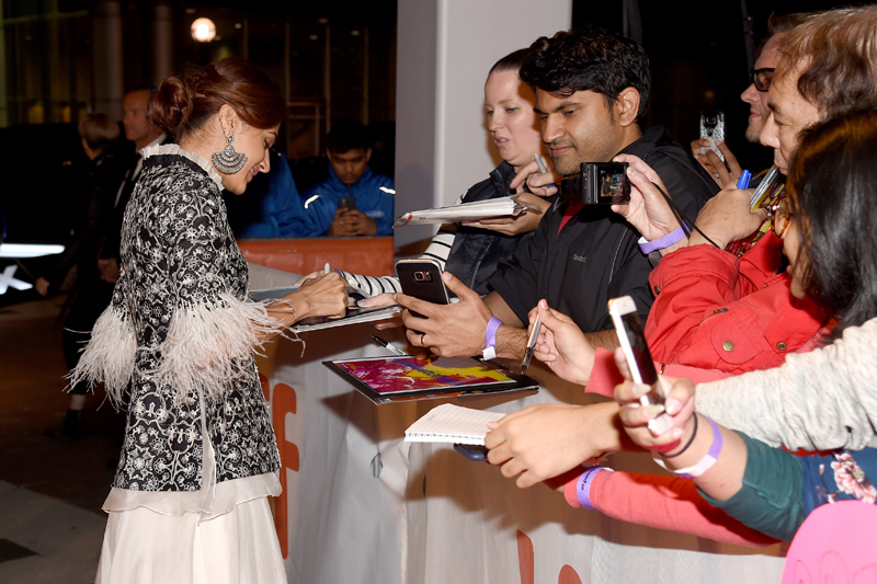 "Taapsee Pannu signs autographs at the premiere of ""Husband Material"" at the Toronto International Film Festival. Photo by Kevin Winter/Getty Images for TIFF."
