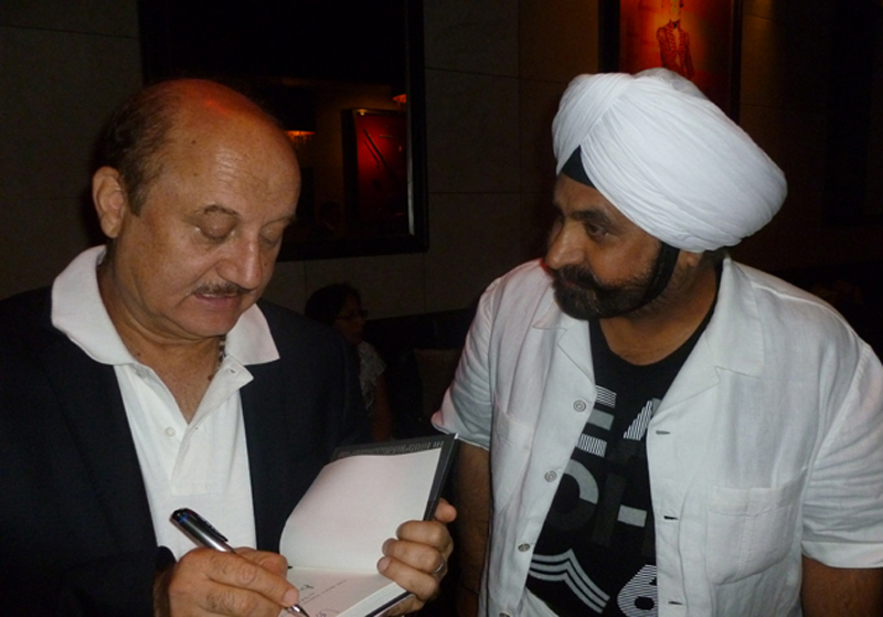 anupam kher signing his book for Nav Bhatia